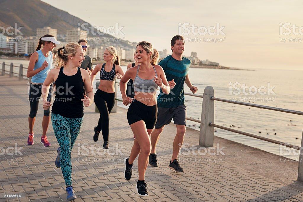 Group of athletes running along a seaside promenade stock photo