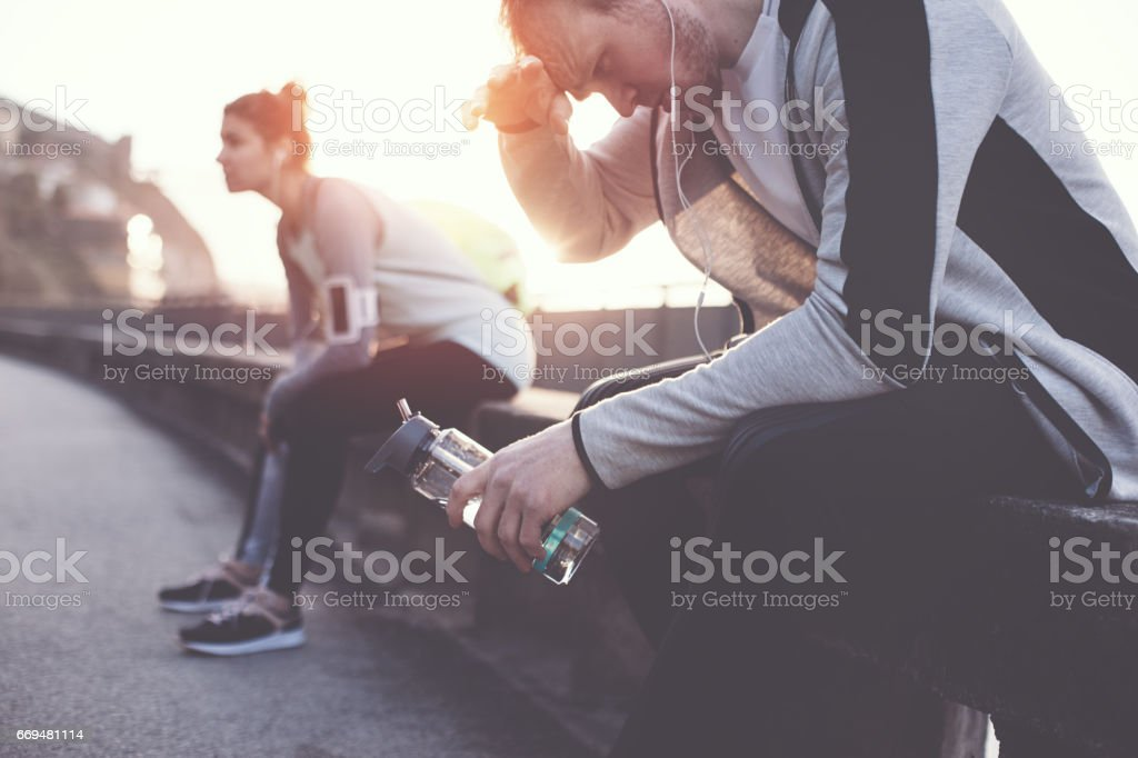 Group of athletes sitting and resting on the street stock photo