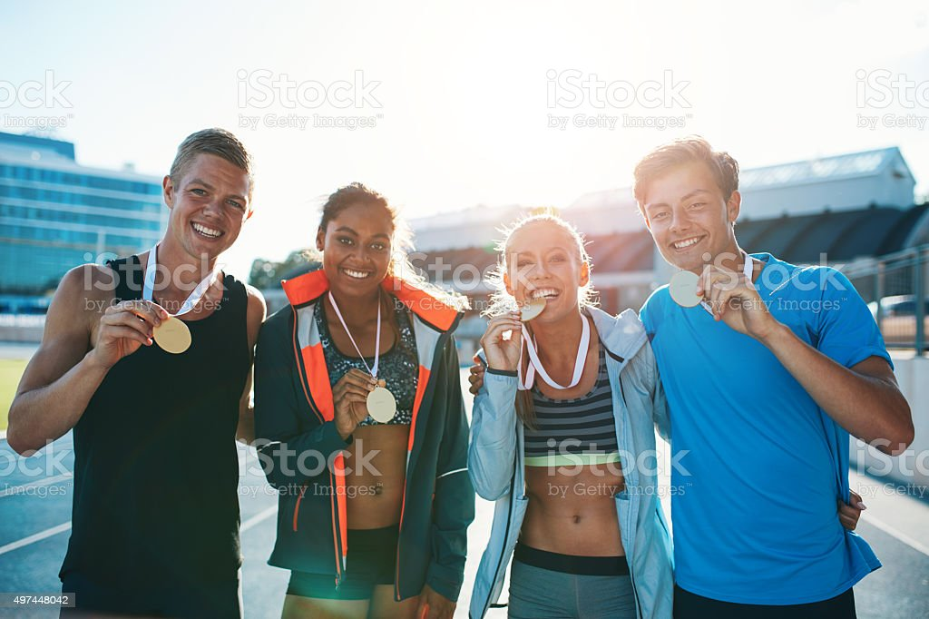 Group of athletes with gold medals looking happy stock photo