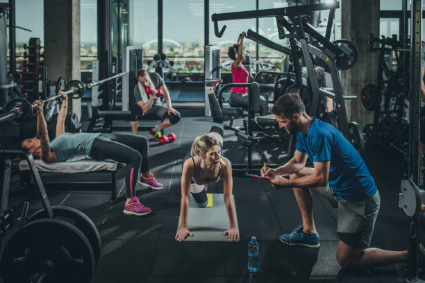 Group of athletic people exercising in a health club. Group of athletic people having a sports training in a gym. Focus is on blond woman exercising and talking to her coach. training equipment stock pictures, royalty-free photos & images