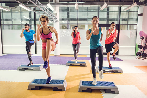 group of athletic people exercising step aerobics in a gym. - aerobics stock photos and pictures