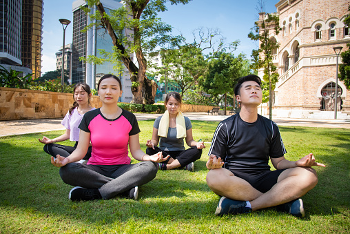 Group of young energetic people practicing yoga in Lotus position with their eyes closed at public park.