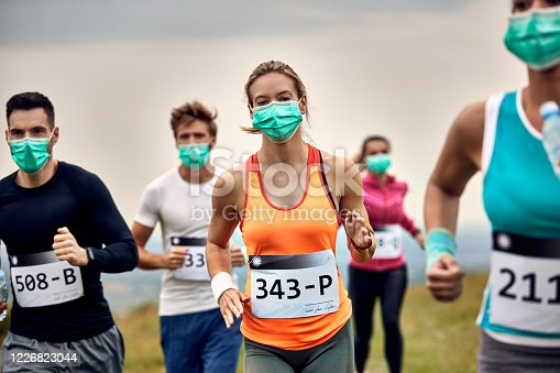 Group of runners wearing face masks while participating in humanitarian marathon during virus epidemic. Focus is on woman in orange shirt.