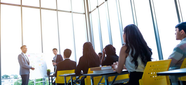 group of attentive adult students with speaker giving a talk or trainer in classroom or seminar at business training to success of target. - training imagens e fotografias de stock