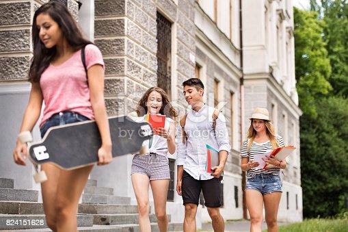 824257318 istock photo Group of attractive teenage students walking to university. 824151628