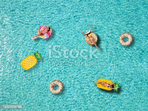 A group of attractive women enjoys the sun on pineapple and doughnut shaped floats over pristine, tropical waters