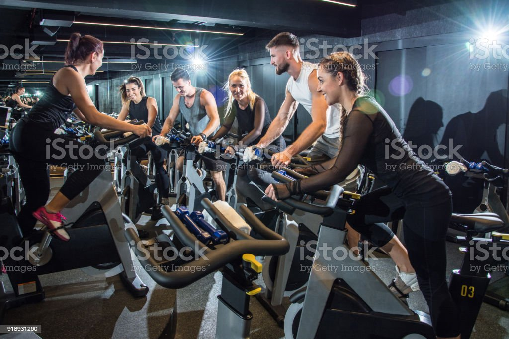 Group of attractive women and men pedaling on a stationary bikes at the gym. stock photo