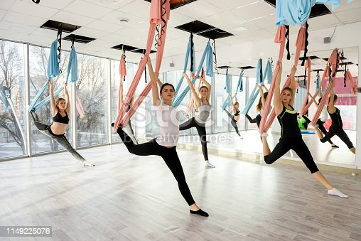 istock Group of attractive women doing fly yoga in gym 1149225076