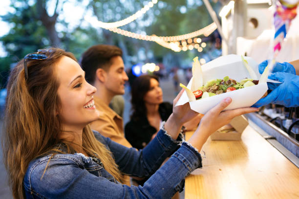 grupo de amigos jóvenes atractivo elegir y comprar diferentes tipos de comida rápida en comer el mercado en la calle. - couple lunch outdoors fotografías e imágenes de stock