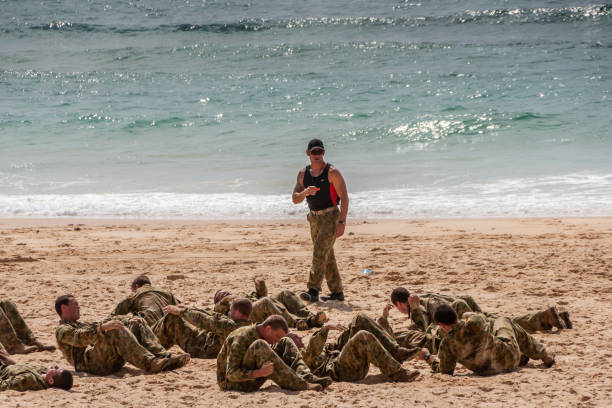 Group of Australian Marines exercise stomach crunch on beach in Newcastle, Australia. stock photo