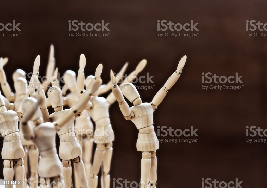 Group of awestruck wooden figures look up, gesturing stock photo