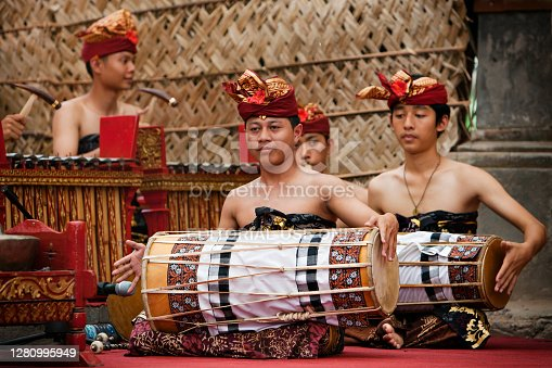 Denpasar, Bali island, Indonesia - June 23, 2016: Group of Balinese people. Beautiful men in colorful costumes play traditional gamelan music on street parade at art and culture festival.