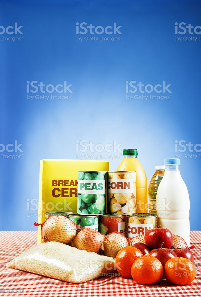 Group of basic foods on red checked cloth against blue stock photo