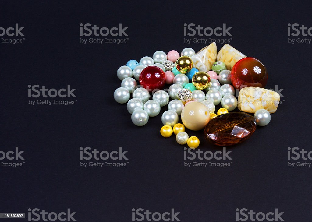Group of beads for manual making jewelry on isolated black stock photo