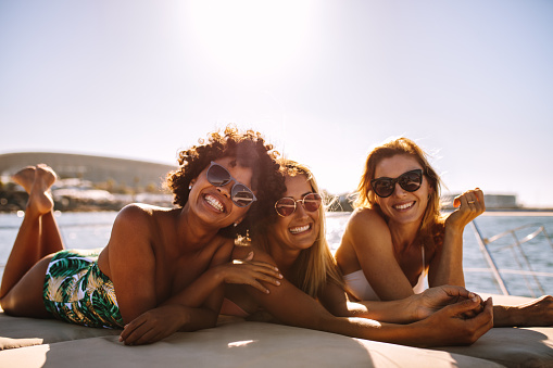 Group of beautiful women relaxing on a yacht deck. Three female friends sunbathing on small boat looking at camera and smiling.