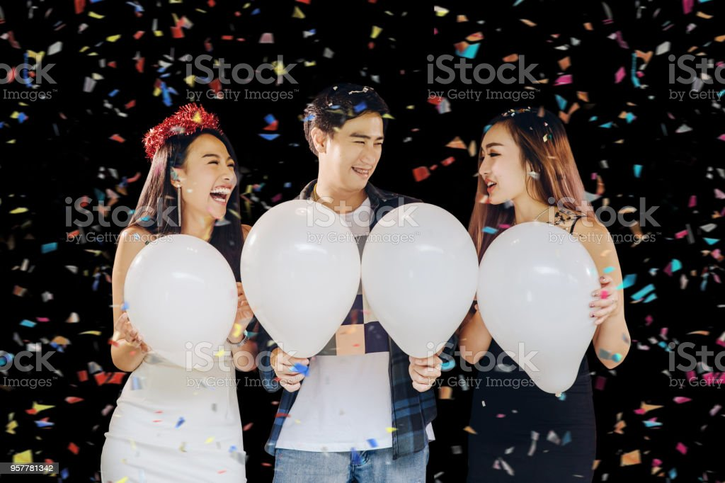 Group of beautiful young asian people celebrating New Year's Eve,and holding white balloons for input your text.happy and funny concept stock photo