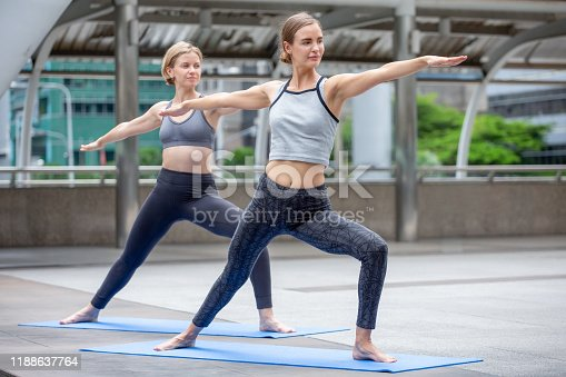 group of  beautiful young fitness women doing yoga stretching arm and leg in urban city outdoors . two friend sport girl exercise together . workout healthy lifestyle. City life concept . slender