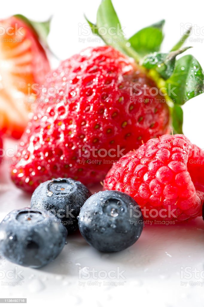 group of berries blueberries,  raspberry and strawberry close-up on white background stock photo