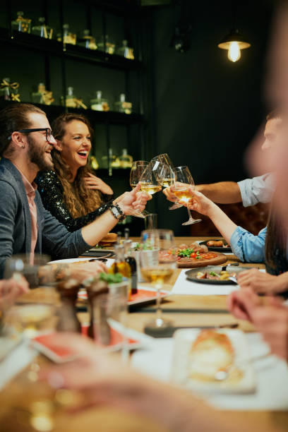 Group of best friends sitting in restaurant, making a toast and celebrating. stock photo
