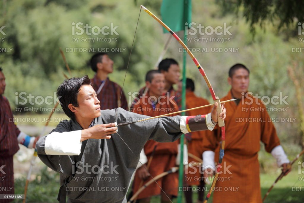 A group of Bhutanese men compete in the national sport of archery a...