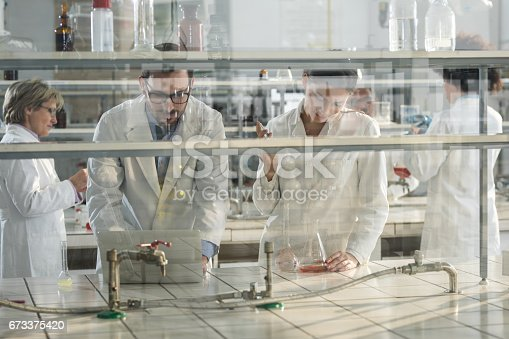 499203366 istock photo Group of biochemists working on a new research in laboratory. 673375420