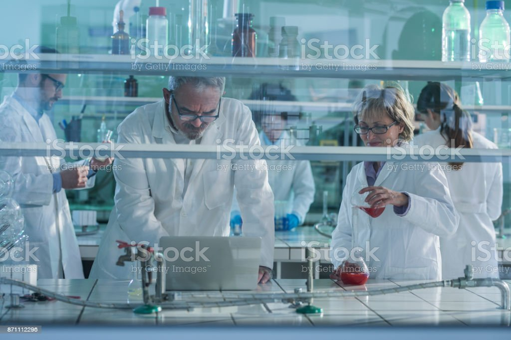 Group of biochemists working on new research in laboratory. stock photo