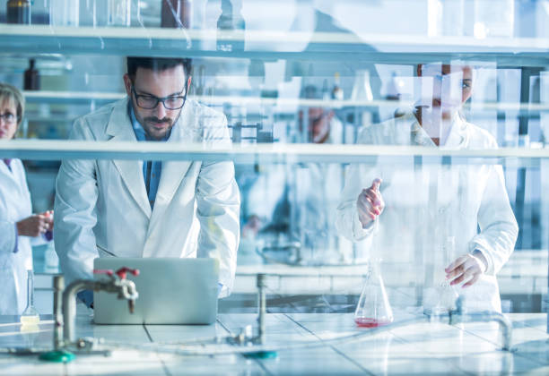 group of biochemists working on new research in laboratory. - ricerca scientifica foto e immagini stock
