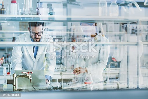 Team of scientists working on scientific research in laboratory. The view is through glass.