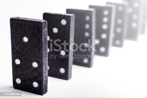 84743203 istock photo A group of black dominoes lined up 1140396340