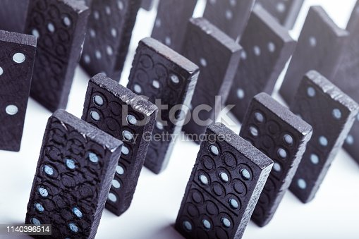 84743203 istock photo A group of black dominoes lined up 1140396514