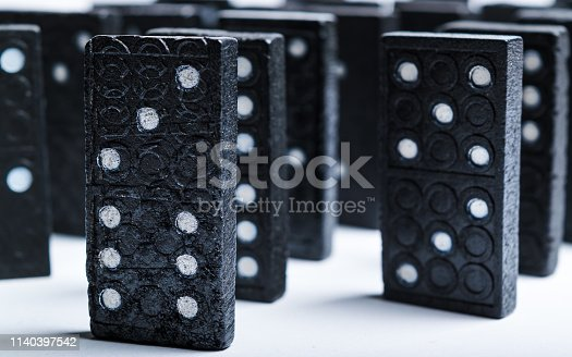 84743203 istock photo A group of black dominoes lined up 1140397542