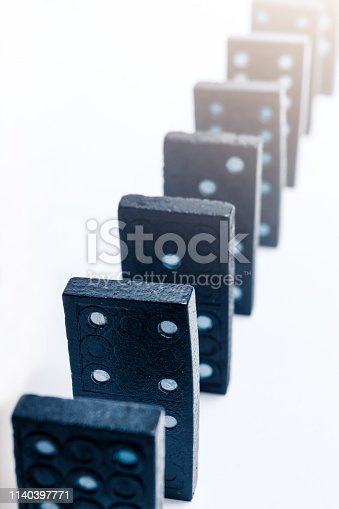 84743203 istock photo A group of black dominoes lined up 1140397771