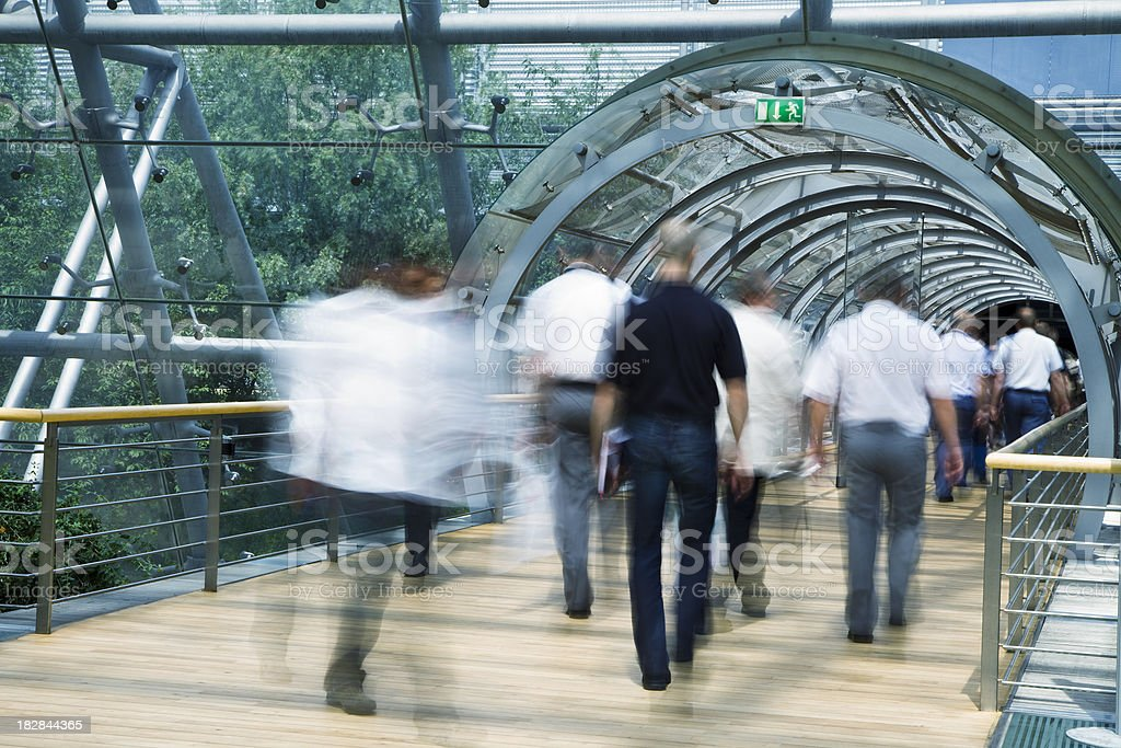 Group of Blurred Businessmen Walking Through Glass Tunnel stock photo