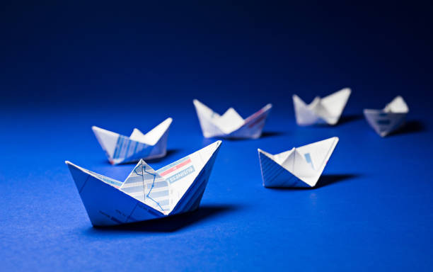 Group of boat paper graph on blue ocean.Business leader concept. stock photo