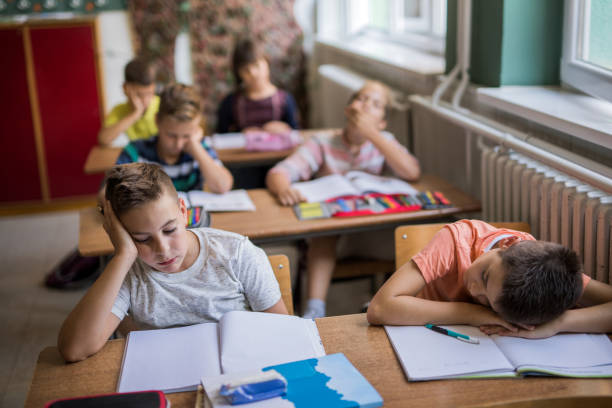 Group of bored elementary students in the classroom. stock photo