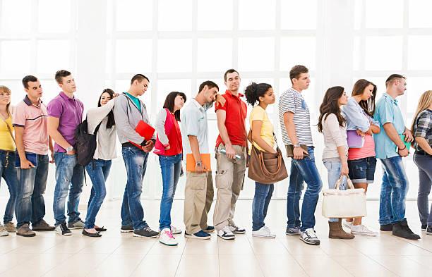 instants groupe d'élèves debout dans une ligne et en attente. - queue photos et images de collection