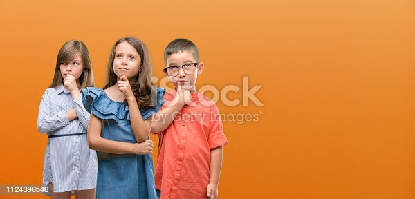 istock Group of boy and girls kids over orange background serious face thinking about question, very confused idea 1124396546