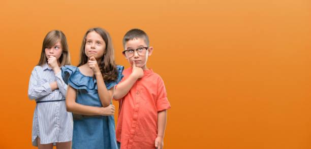 gruppe von jungen und mädchen kinder über orangefarbenen hintergrund ernstes gesicht über frage, sehr verwirrte idee - fragen für jungs stock-fotos und bilder