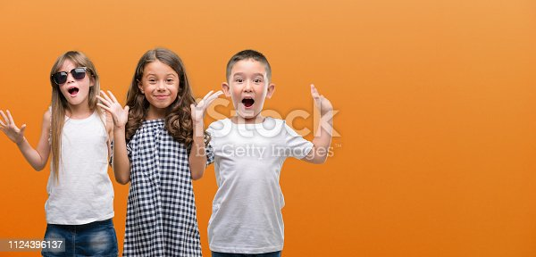 istock Group of boy and girls kids over orange background very happy and excited, winner expression celebrating victory screaming with big smile and raised hands 1124396137
