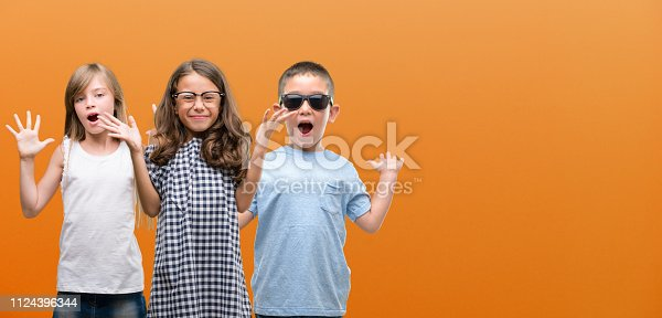 istock Group of boy and girls kids over orange background very happy and excited, winner expression celebrating victory screaming with big smile and raised hands 1124396344