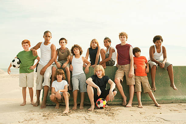 Group of boys by wall with football, portrait stock photo