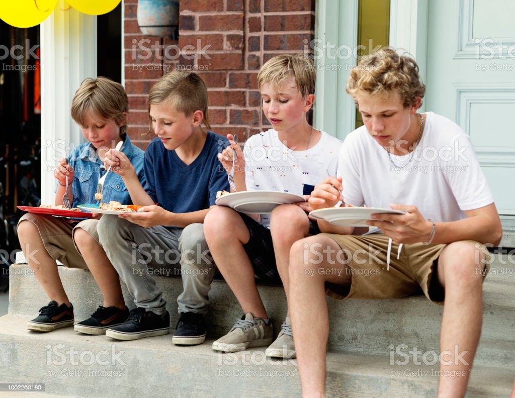 Group of boys eating on home porch. stock photo
