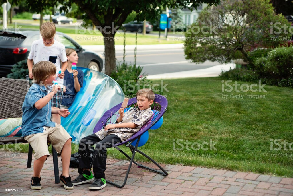 Group of boys eating popsicle in suburb driveway in summer. stock photo