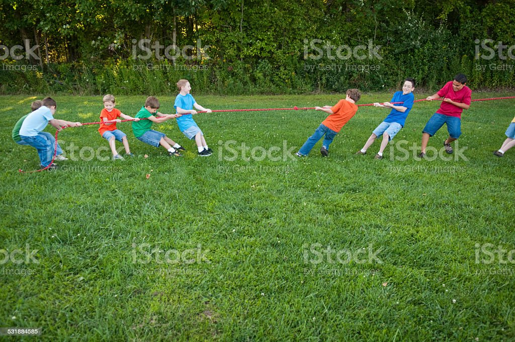 Color photo of a group of boys playing a tug-of-war competition...