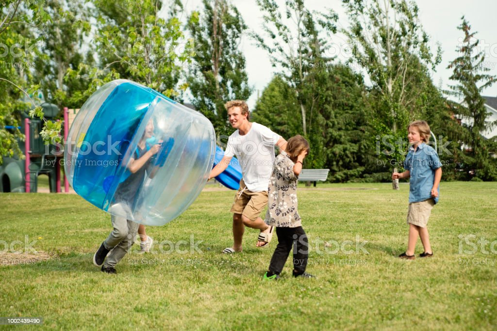 Group of boys running and playing in suburb park. stock photo