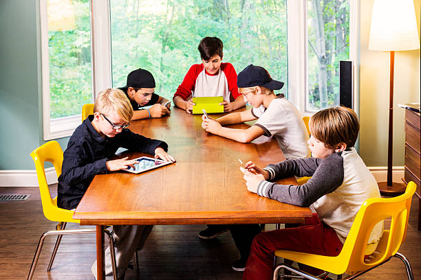 group of boys using digital devices for recreation - mobile game stock photos and pictures