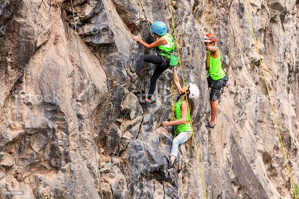 Group Of Brave Climbers Climbing A Rock Wall stock photo