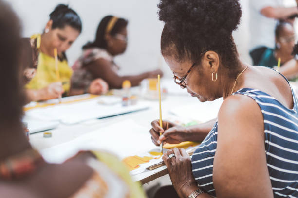 group of brazilian women painting textiles in work room of social project stock photo
