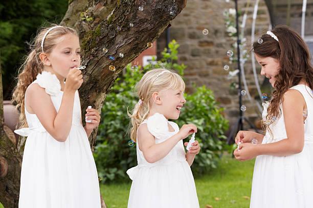 gruppe von brautjungfern blasen blasen im garten - hochzeitsfeier mit kindern stock-fotos und bilder