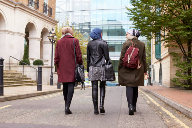 Group Of British Muslim Businesswomen Returning To Office Group Of British Muslim Businesswomen Returning To Office religious veil stock pictures, royalty-free photos & images